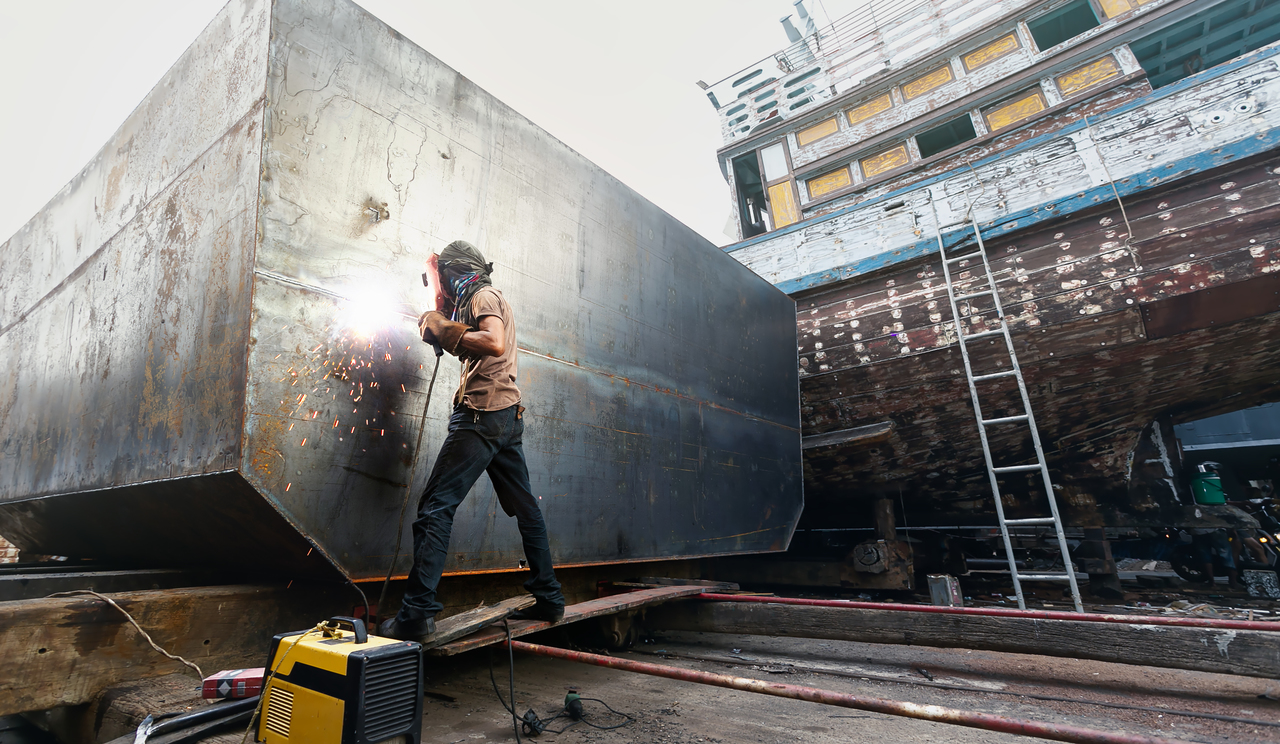 A man welding steel on to a ship