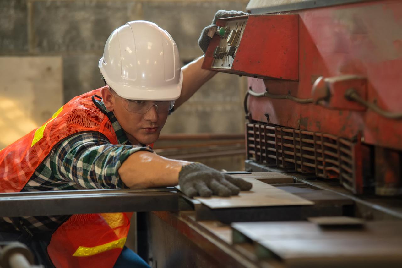 Worker in uniform operating in manual lathe in metal industry fa