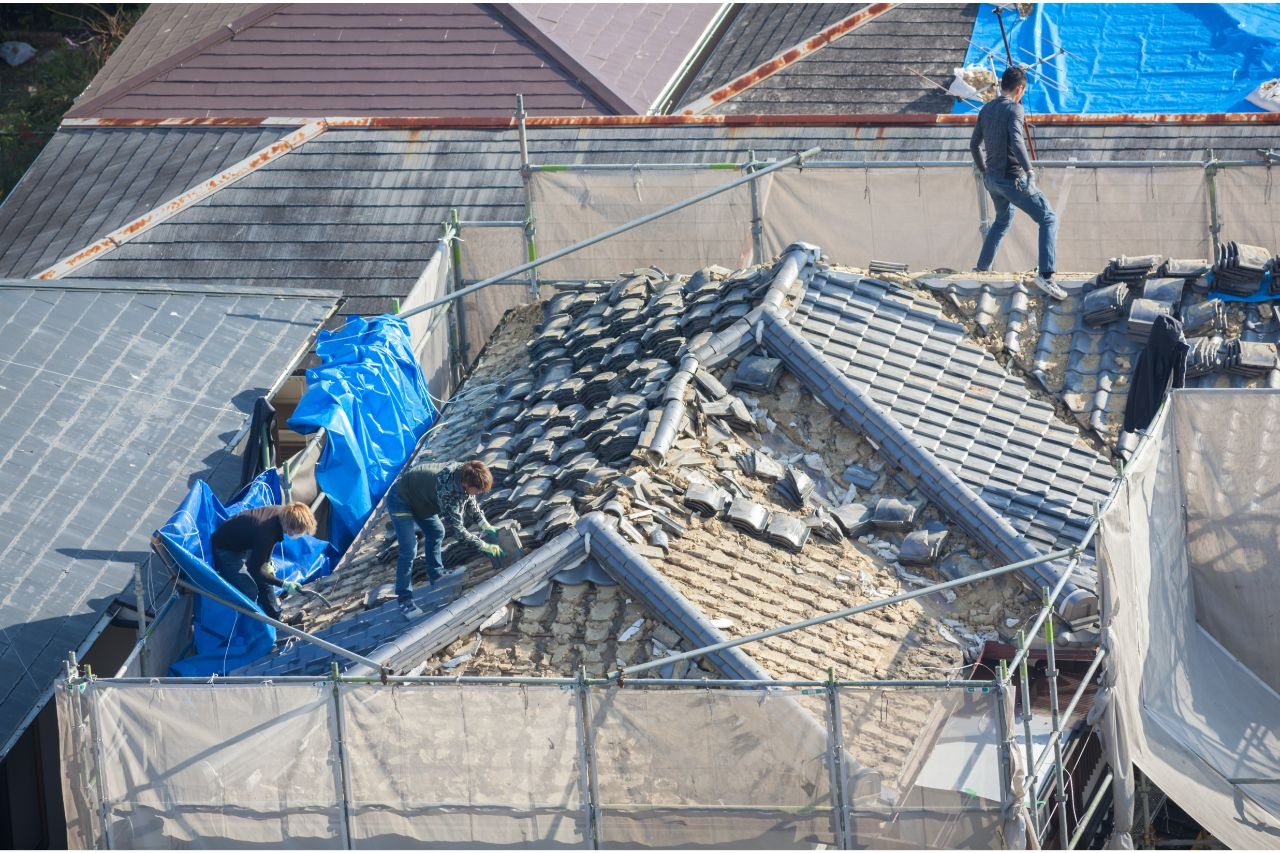 People working on a roof damaged by natural disaster
