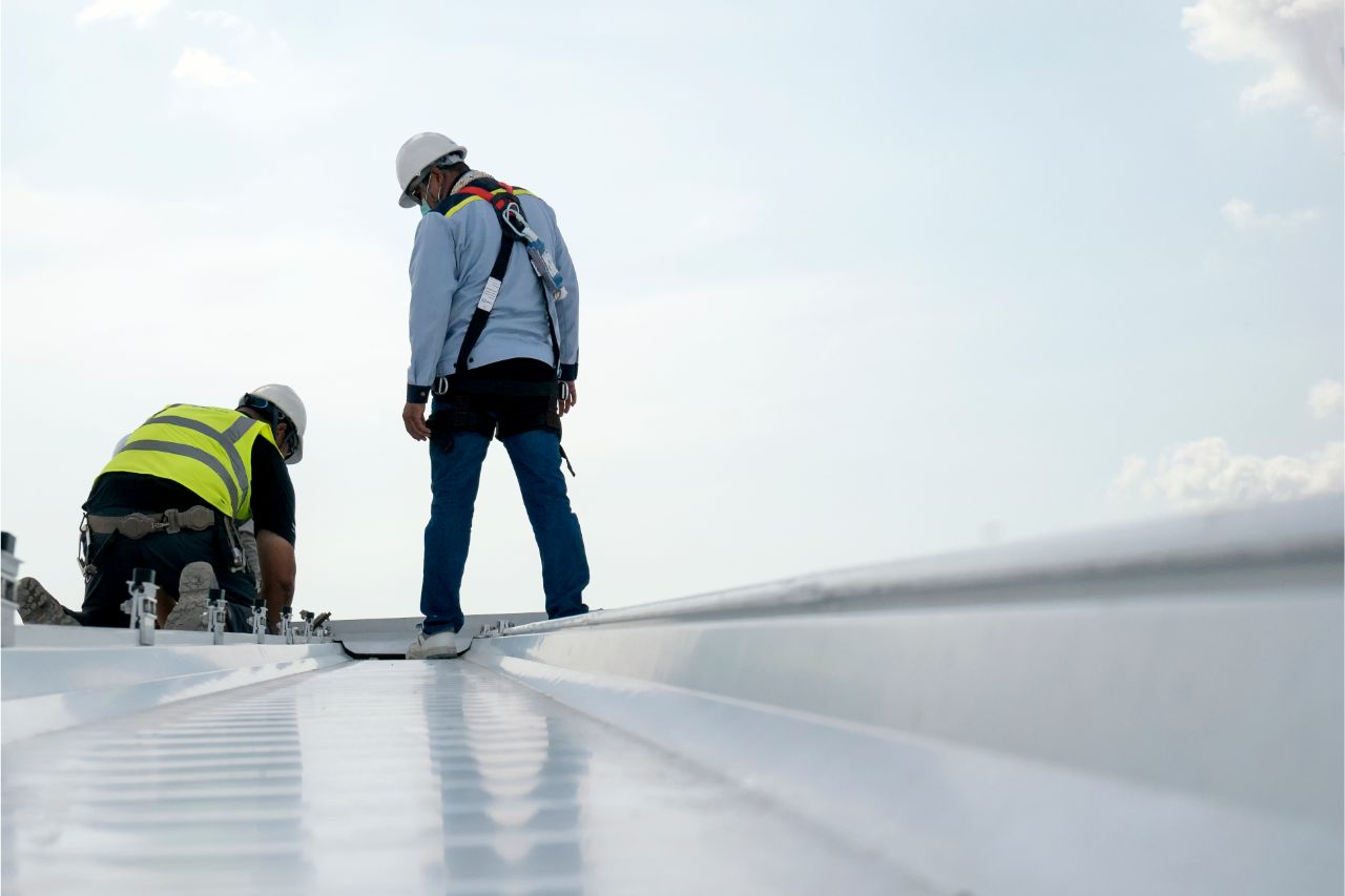 Construction workers installing a corrugated metal roof