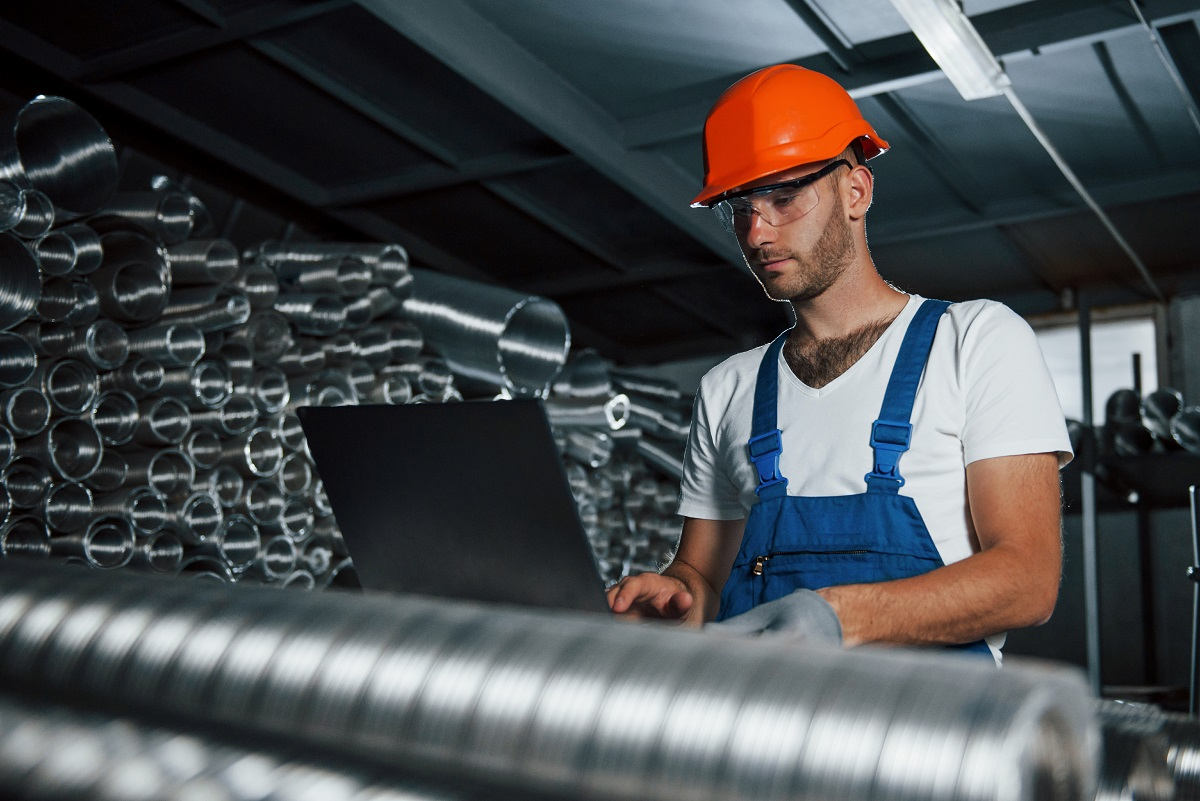Production of metal pipes. Man in uniform works on the production. Industrial modern technology