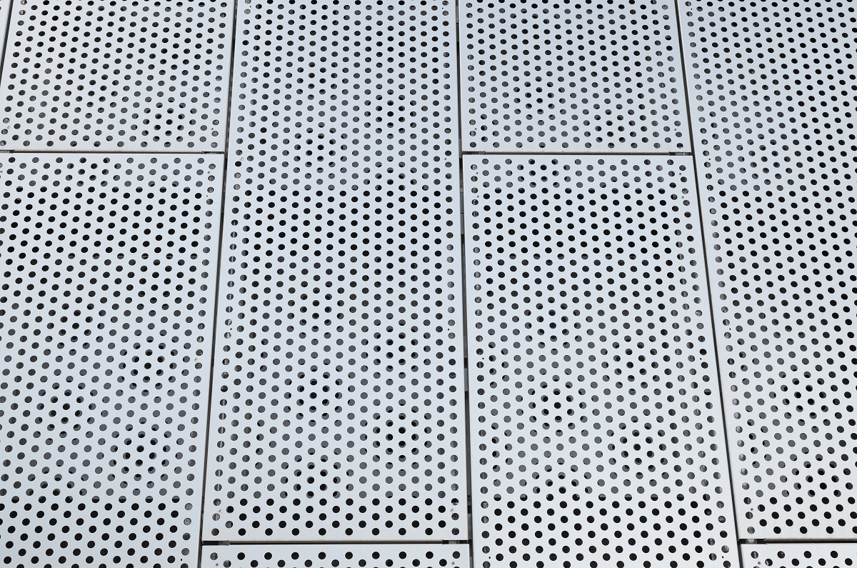 Metal grilles with many round holes in the ceiling. Dot pattern on surface.